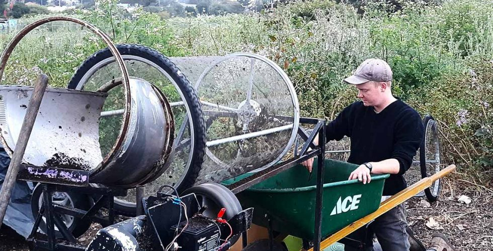 Worker uses sifting device to process finished compost into a wheelbarrow.